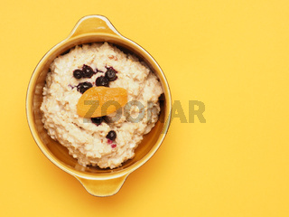Delicious organic porridge with blueberries and apricot on a yellow table