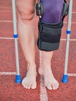 Woman suffering with walk by sticks and knee brace support surgery