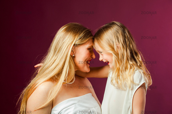 Portrait of mother and daughter isolated on purple background