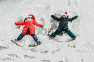the cute little kids make snow angel on the ground