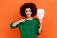 Satisfied woman with Afro hairstyle wearing green casual style sweater pointing finger to white mask in her hand, wants to change personality.
