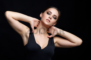 Beauty portrait of young woman with hands on neck on black background.