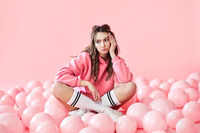 Bored fashionable woman sitting on floor with pink air balloons on pink pastel background