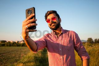 Happy young man taking selfie in summer field