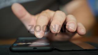 Die Finger einer Person bedienen ein Smartphone