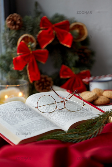 close up of open book and glasses on christmas
