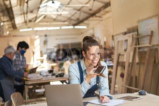 Handwerker Frau mit Smartphone und Laptop