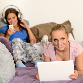 Girls lying bed with laptop and headphones