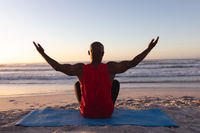 Rear view of senior african american man with arms wide open practicing yoga at the beach