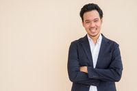 Portrait of Asian businessman wearing suit against plain background and smiling