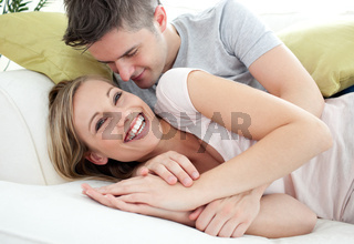 Joyful lovers having fun together on a sofa