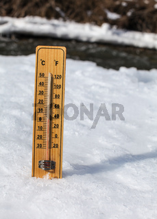 Wooden thermometer standing in ice on partially frozen river, sun shining, showing +3 degrees. Image to illustrate winter leaving, snow slowly thawing, warmer days coming