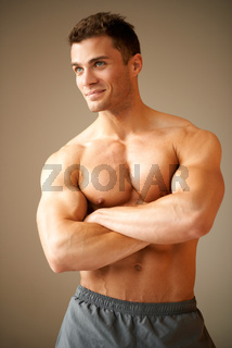 Smiling handsome man with muscular arms crossed