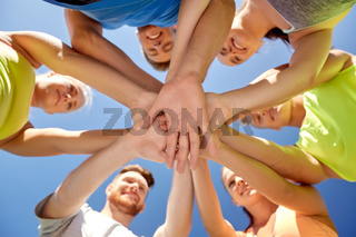 group of happy sporty friends stacking hands