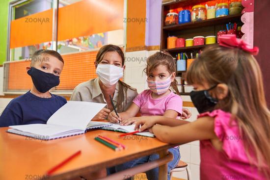 Kinder und Erzieherin in einer Kita mit Mundschutz