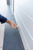 Hand with a key closing a roller shutter door of a store. Closing concept
