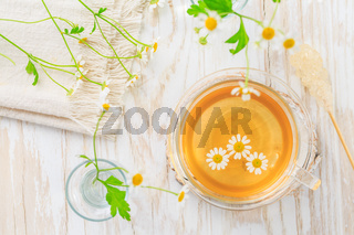 Cup of Chamomile tea on wooden kitchen table.