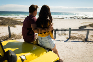 Happy caucasian couple sitting in beach buggy looking towards sea