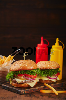 Two homemade burgers with beef, cheese and onion marmalade on a wooden board, fries in a metal basket and sauces. Fast food concept, american food
