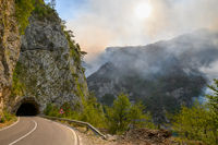 Road and tunnel at Piva Lake in national park Dormitor of Montenegro during wildfire at the end of summer