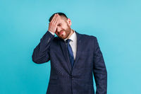 Portrait of upset bearded man wearing official style suit standing with facepalm gesture, blaming himself, feeling sorrow regret because of bad memory.