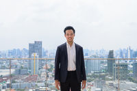 Portrait of Asian businessman wearing suit at rooftop in city