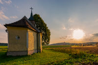 Typical Bavarian rural farm labor scene with small chapel, tractor plowing field  and pilgrimage church on top of hill in background in evening sunlight with flying dust particles in thei air