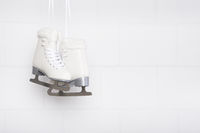 Pair of white figure skates for females hanging at a white concrete background with space for copy
