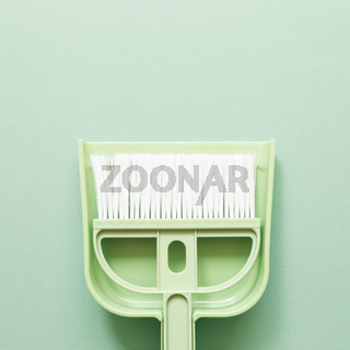 Green broom and dustpan on green background. Cleaning housework concept. top view, copy space