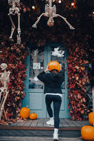 Girl with a pumpkin head posing at the door on the street