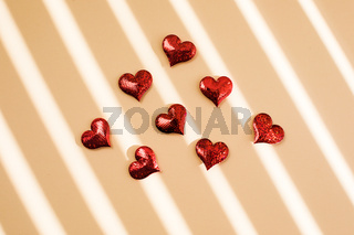 Red sparkle hearts scattered on the beige background