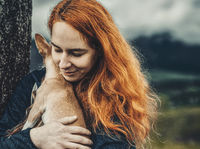 woman with a little dog in her arms.