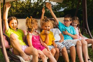 Children sitting on large swing in backyard