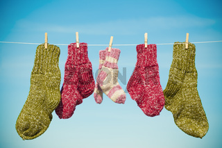 Three pairs of woolen socks hanging on rope