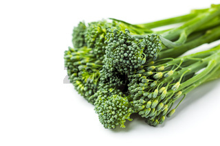 Raw broccolini heap isolated on white background