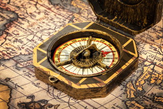 Vintage pirate retro compass close up on ancient world map