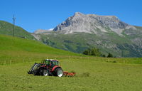 a tractor working in the fields high in the mountains