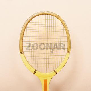 Vintage wooden tennis racket against pink wall
