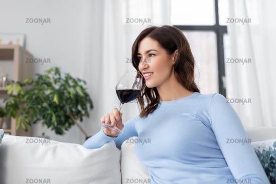 happy woman drinking red wine at home