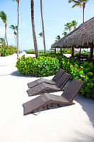 Relax on tropical beach in the sun on deck chairs under umbrella.