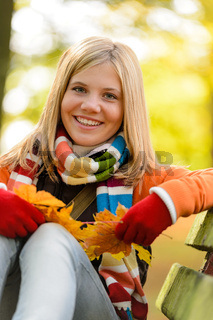 Autumn cheerful young girl sitting park fall