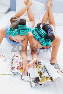 Girls in hair rollers lying in bed and reading