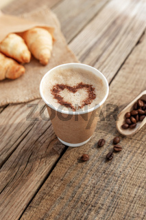 Paper cup of coffee with heart, croissants, beans and spoon at wooden table