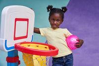 Mädchen steht mit einem Ball am Basketball Netz