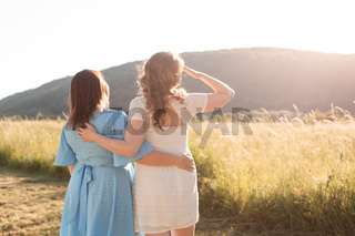 Two adult girlfriends hug each other at the background of nature