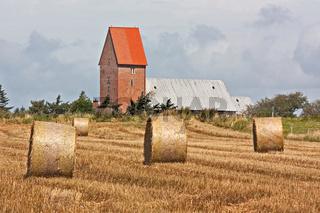 Strohballen auf Getreidefeld auf Sylt. Im Hintergrund die Kirche von Keitum.