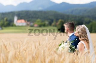 Bride hugs groom tenderly in wheat field somewhere in Slovenian countryside.