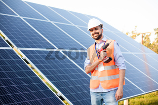The young electrician works at a solar station