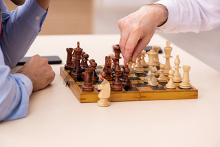 Two businessmen playing chess in the office