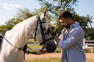 The handsome man is looking into the eyes of a horse